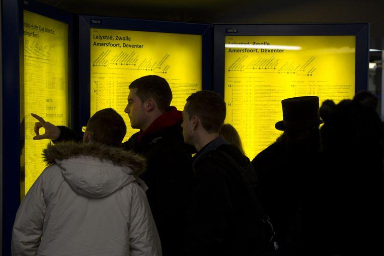 Treinreizigers bekijken de dienstregeling van de Nederlandse Spoorwegen. Beeld ANP