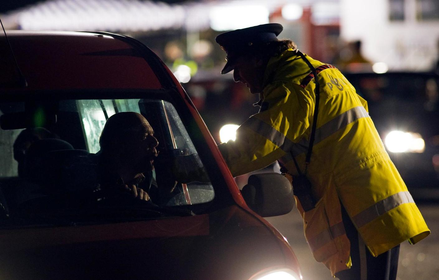 Een automobilist moet blazen tijdens een controle.