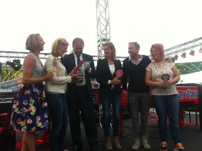 Wethouder Jan Hoskam met de eigenaren en medewerkers van snoeperij Tum Tum bij de uitreiking van een ondernemers-trofee.