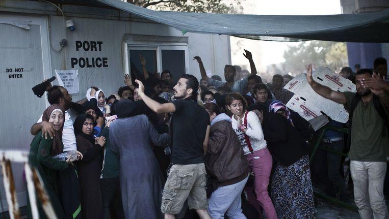 Syrische en Afghaanse vluchtelingen proberen zich te registeren op het Griekse eiland Lesbos, maar worden bekogeld met stenen. Beeld afp