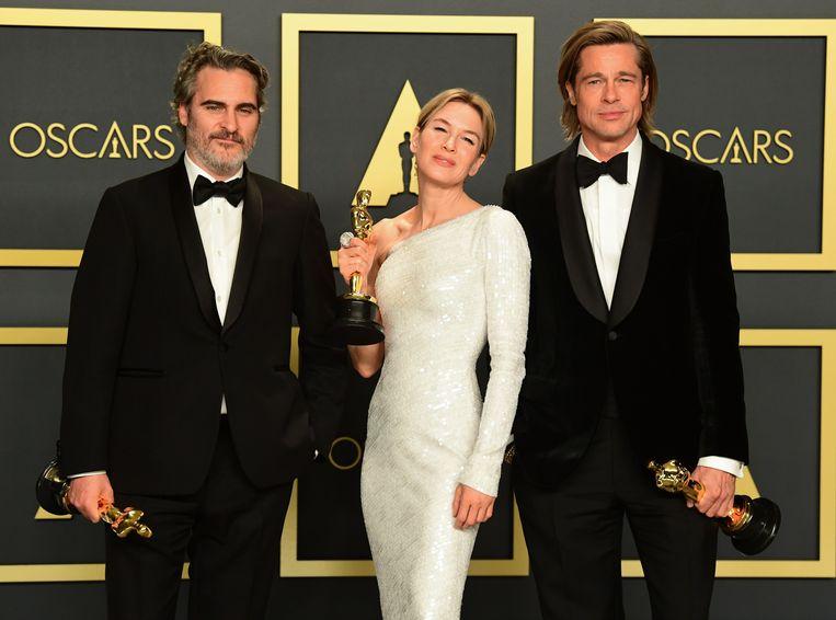 Joaquin Phoenix (beste acteur), Renee Zellweger (beste actrice) en Brad Pitt (beste mannelijke bijrol) met hun Oscars.  Beeld AFP