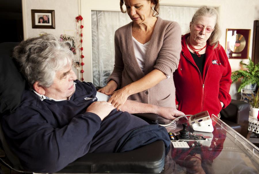 Een thuishilp meet de bloeddruk van een zieke man.