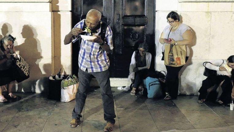 Arme Portugezen eten uitgedeeld voedsel op een plein in Lissabon. De kloof tussen Noord- en Zuid-Europa is groot. Beeld ap