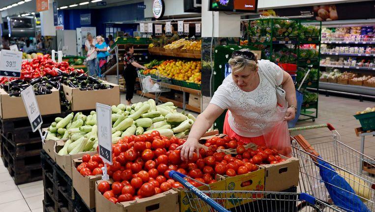 Een vrouw pakt een tomaat uit een doos in een supermarkt in Moskou. Beeld epa
