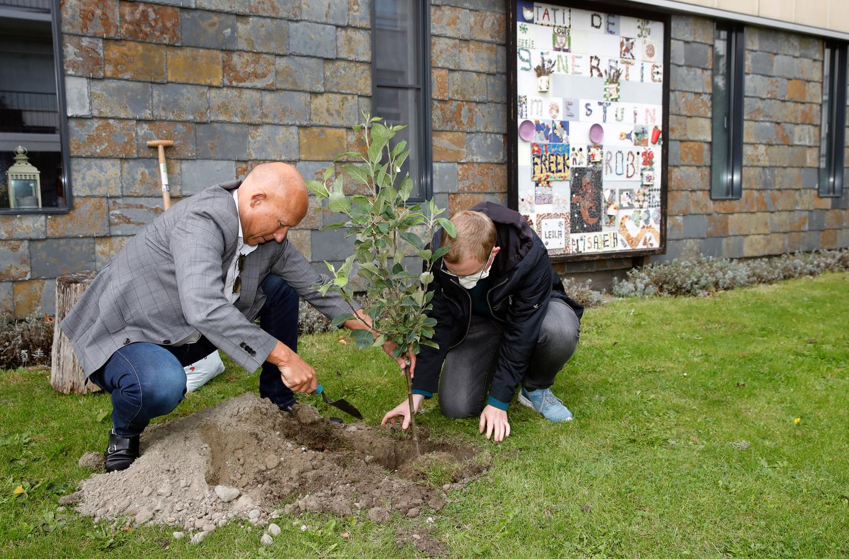 Wethouder Jan Willem Mijnans (ONS) en Milan Votsis planten een appelboom in de generatiemoestuin in Spijkenisse.