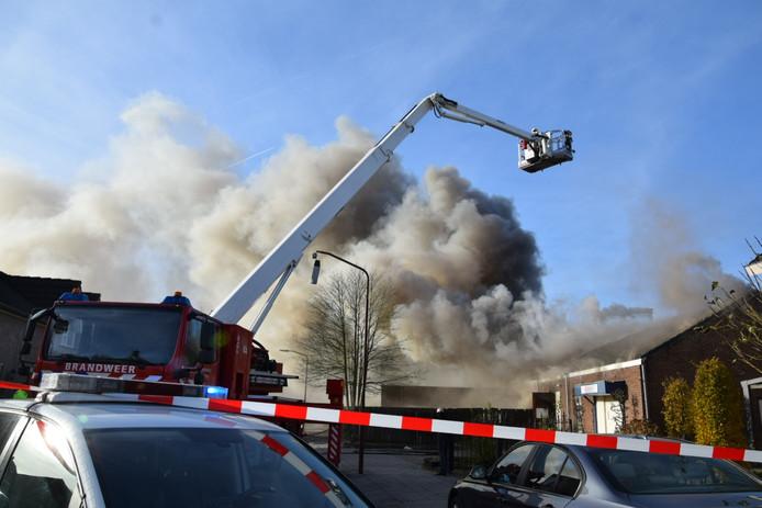De uitslaande brand woedt in een opslagloods naast een woning.