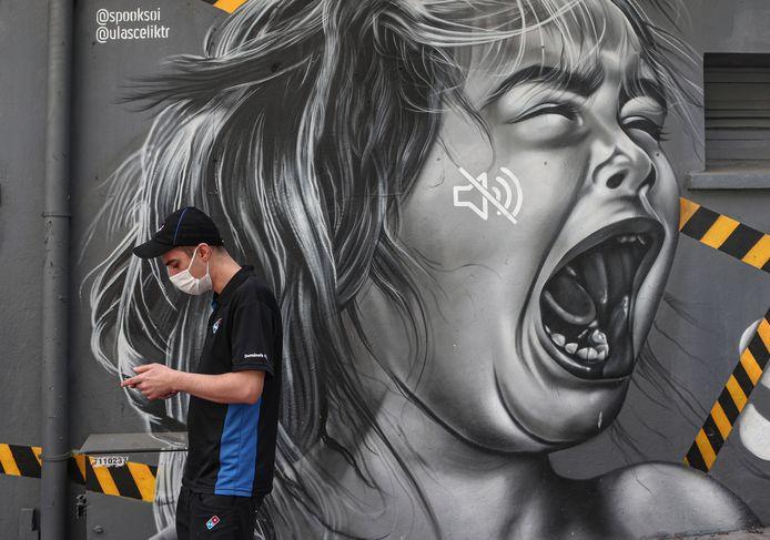 Een man met een mondmasker wandelt langs een muurschildering die aandacht vraagt voor kindermishandeling tijdens de lockdown.