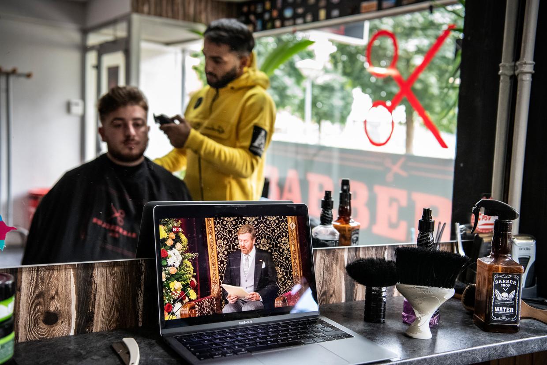 Nederland,Nijmegen,17-09-2019kapper Eti Bachsijev kijkt met klant naar troonrede. foto Koen Verheijden.
