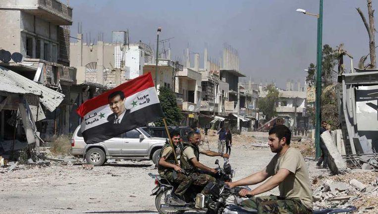 Troepen die loyaal zijn aan president Assad rijden door de straten van het belegerde Qusair. Beeld reuters