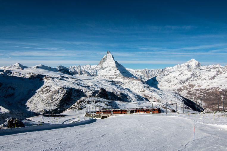 Trein rijdt door het alpengebied met in de achtergrond de Matterhorn.  Beeld Getty Images/iStockphoto