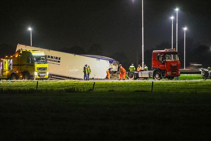 Bergers scheppen zand weg rond de losgeraakte trailer op knooppunt Beekbergen.