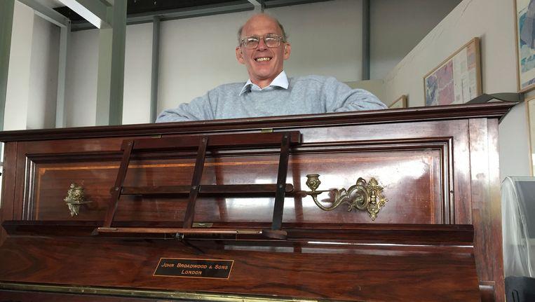 Pianostemmer Martin Backhouse met het instrument waarin hij de enorme hoeveelheid gouden munten vond.