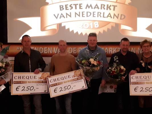 Marktmeester Martin Wippert en voorzitter Jaco Zwaan van de Nijverdalse marktkooplieden (middenin) zijn trots op het behalen van de tweede prijs in de categorie middelgrote markt.