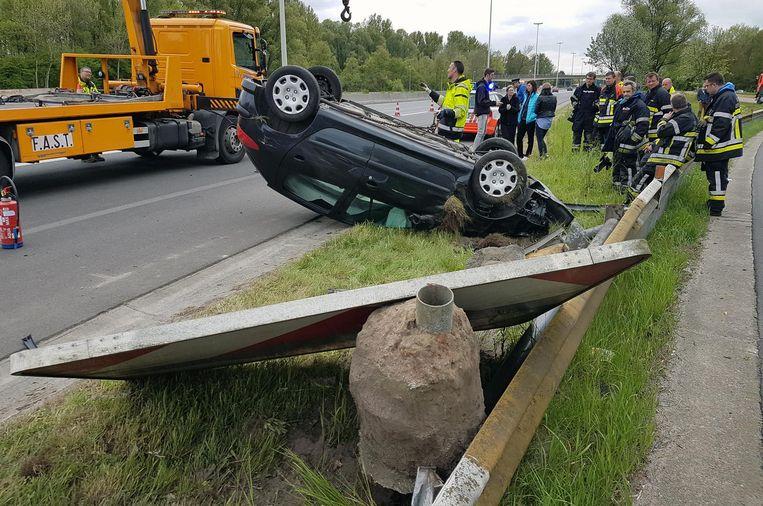 De Peugeot ligt op zijn dak. Het signalisatiebord is uit de grond gerukt.