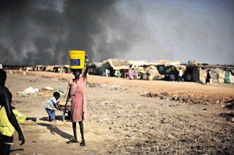 Een meisje haalt water in een emmer van een hulporganisatie. Het water komt uit tankwagens, want de bronnen zijn vervuild door olie. (FOTO AFP) Beeld