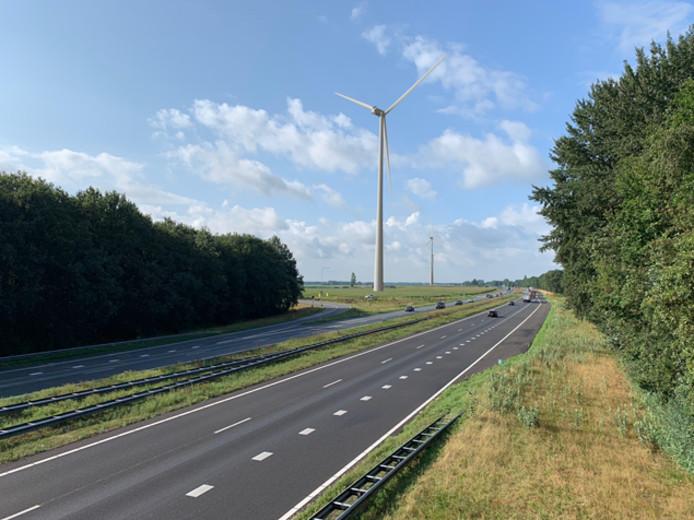 Impressie van windmolens langs een snelweg.