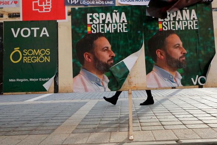 Een vrouw loopt achter posters van het extreemrechtse VOX, met een afbeelding van Santiago Abascal, langs.