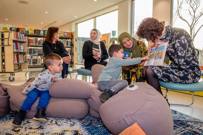 Turkse moeders Vesik Macit (rechts) en Semra Saruhan (tweede van rechts) lezen voor in de bibliotheek.