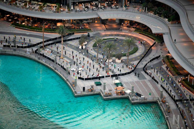 Mensen houden afstand terwijl ze de fonteinenshow in Dubai bekijken.