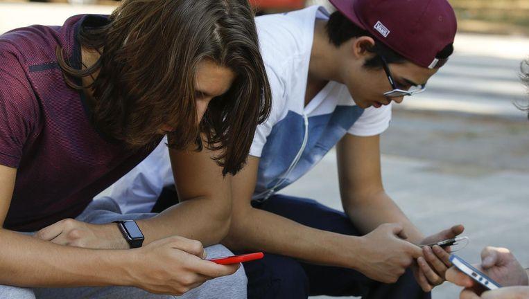 Jongeren in Sao Paulo zijn bezig met hun telefoon. WhatsApp is razendpopulair in Brazilië.