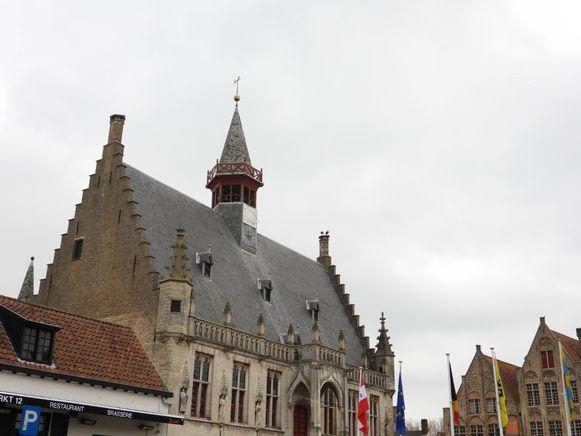 De ooievaars zitten op de schouw van het stadhuis van Damme
