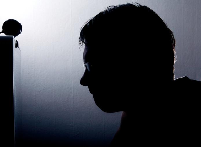 Foto ter illustratie. Een man kijkt naar zijn webcam.