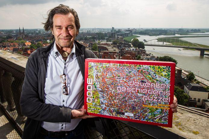Hans Stempher op de Lebuinustoren met de puzzel van zijn tekening waarop hij naar eigen zeggen de volledige geschiedenis van Deventer heeft afgebeeld.