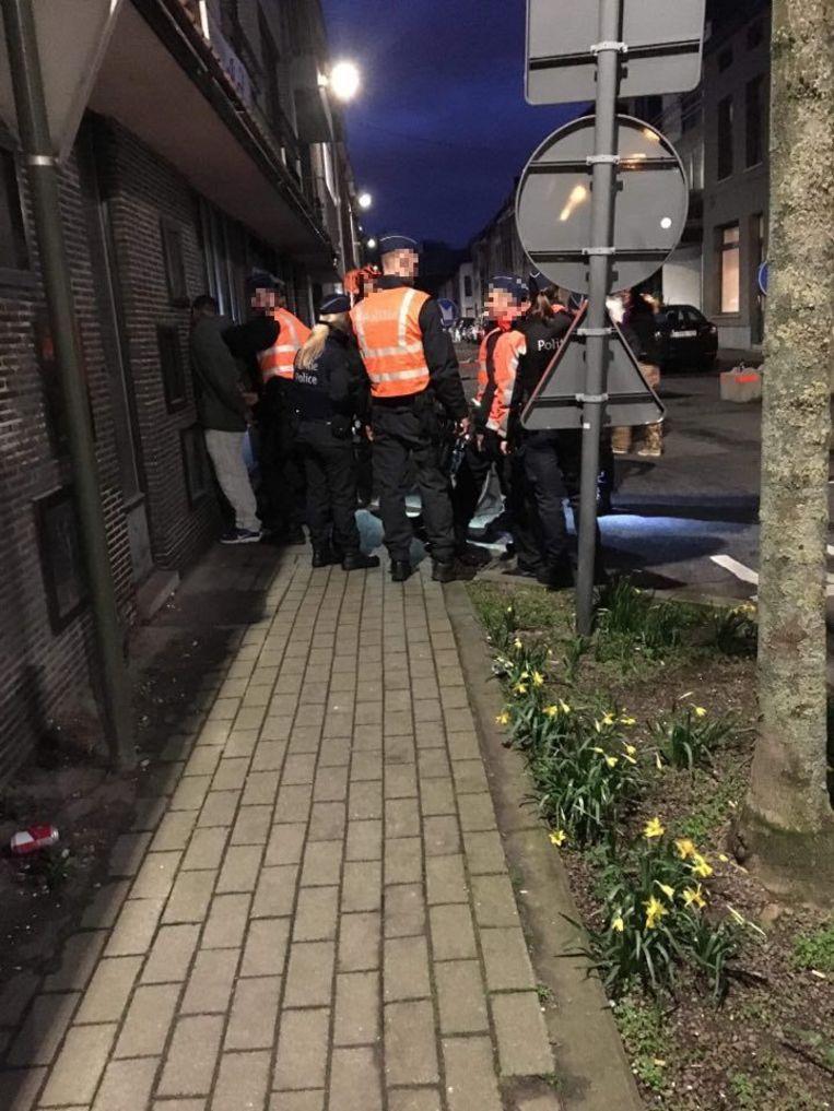 De man wordt door verschillende agenten tegen de muur geduwd en meegenomen.