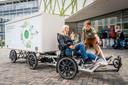 Wethouder Liesbeth van Tongeren op de eerste elektrische grondstoffenfiets om de spatmaskers van hergebruikt plastic af te leveren bij het HagaZiekenhuis.