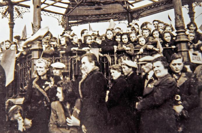 Koningin Wilhelmina bezoekt op 15 maart 1945 Schoondijke. Midden vooraan (vijfde van rechts) staat moeder Marie Huigh-van der Meulen. Achter het hekwerk van de muziektent staat Siem (met bril) midden vooraan.