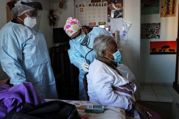 Medisch personeel onderzoekt de longen van een 84-jarige patiënte, die moeite met ademen heeft en andere Covid-19-symptomen vertoont.