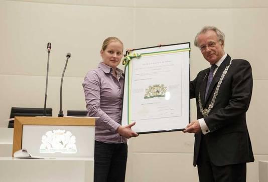 Burgemeester Jozias van Aartsen en voorzitter van het presidium van de Haagse raad Lobke Zandstra tonen het nieuwe stadswapen van Den Haag.