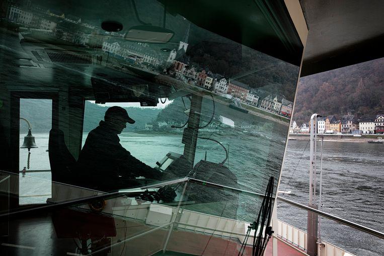 Kapitein Volker Ulrich achter het stuur van de Loreleypont in Sankt Goarshausen. Beeld Daniel Rosenthal