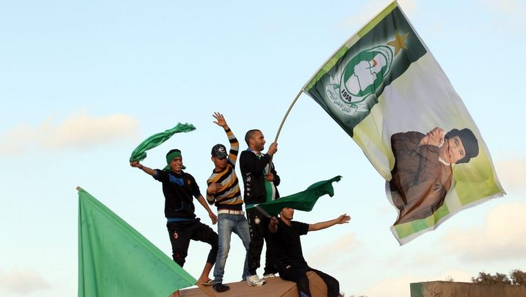 Pro-Kadhafi-betogers in Tripoli, vlakbij het zwaarbeveiligde complex waar de Libische leider zich zou bevinden (boven en onder). Beeld epa