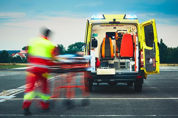 Een ambulancebroeder rusht een brancard met een patiënt erop naar een ambulance.