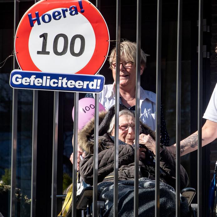 Mevrouw Mali-Geijsberts geniet vanaf haar balkon van de aubade. Ze is vandaag 100 jaar geworden, maar mag in het verpleeghuis geen bezoek ontvangen.