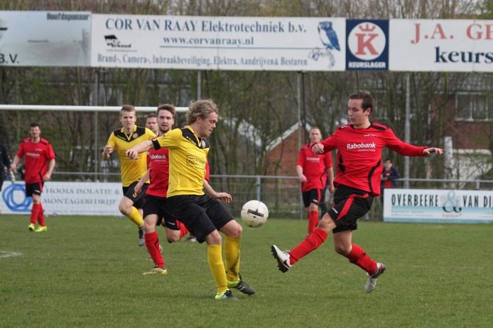 Een speler van Tholense Boys (gele shirts) en van Noad'67 duelleren om de bal in hun derby.