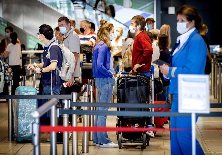 Reizigers arriveren met mondkapjes op Schiphol. Vorige week werd bekend dat ten minste 45 vliegtuigen in Nederland zijn geland met één of meer besmettingen aan boord. Beeld EPA