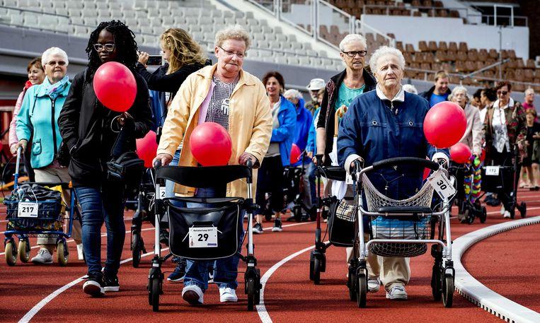 Sportieve senioren nemen deel aan de rollatorloop in het Oympisch Stadion.  Beeld ANP