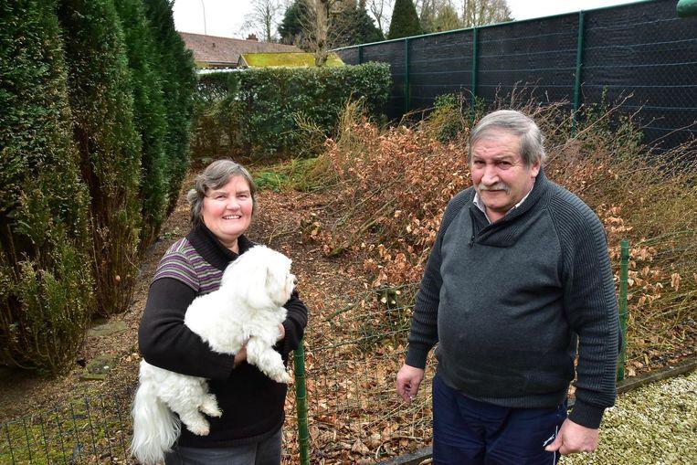 Gerda Castelein en Ronny Delbecke in hun tuin. In de berg snoeiafval achter hen raakt een van de broers verstrikt. Wat later vat de politie ook de andere man.