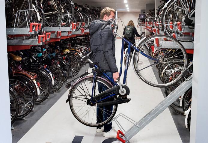 Een fietser heeft een plekje voor zijn fiets gevonden in de overvolle fietsenstalling bij het station