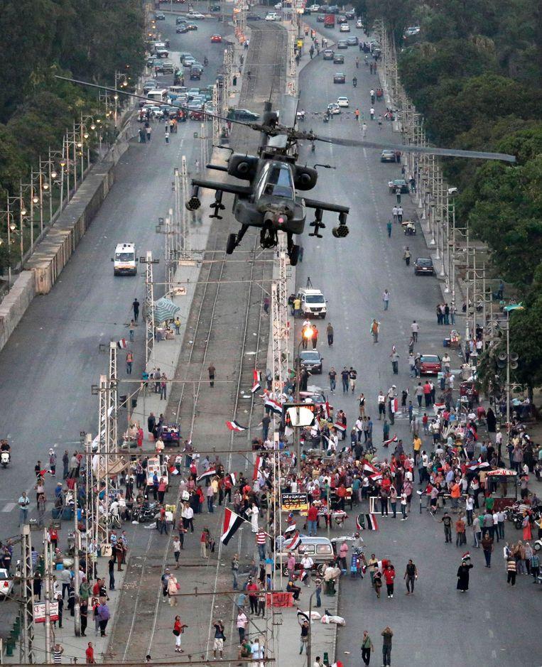 Een helikopter van het Egyptische leger vliegt over een straat in de buurt van het presidentieel paleis in Caïro. Beeld ap
