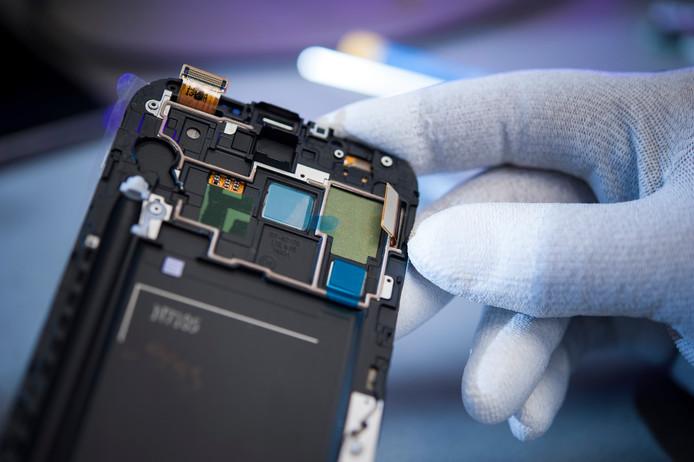 Een tweedehands smartphone wordt geïnspecteerd.