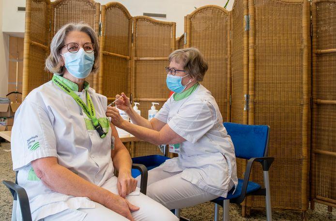 Verpleegkundige Hanny Corstanje krijgt haar vaccin toegediend van Anneke Jol.
