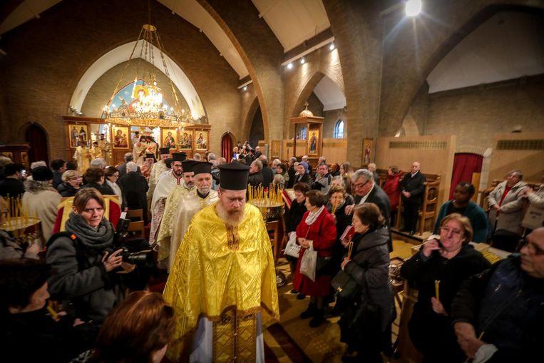 De geestelijken komen de kerk binnen terwijl de orthodoxe geloofsgemeenschap toekijkt.