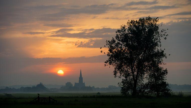 Zonsopkomst boven het Hollandse landschap van het Utrechtse dorpje Schalkwijk op een van de warmste dagen van het jaar. Beeld anp