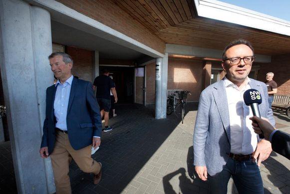 Sauwens verlaat het stemkantoor en loopt even in beeld terwijl Steegen geïnterviewd wordt.
