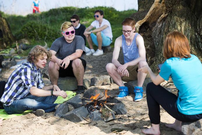 Jongeren barbecueën op een Waalstrandje.