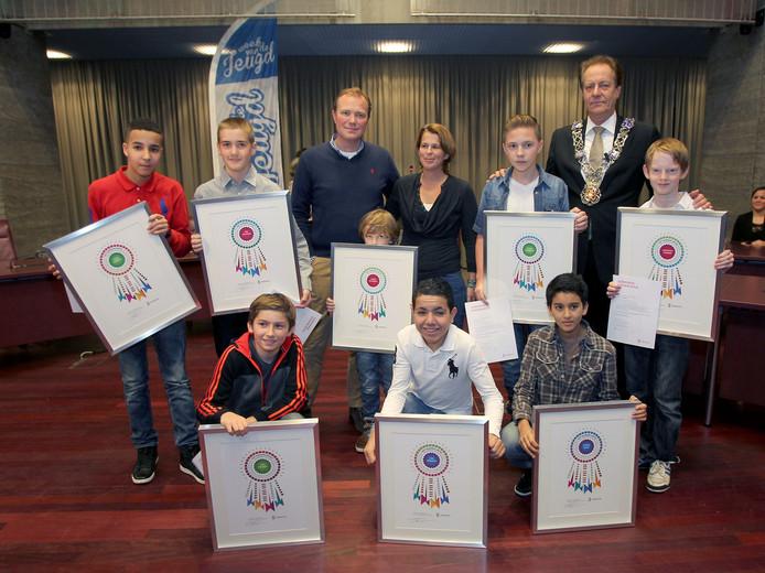 Archieffoto. Eindhoven heeft eenmaal kinderlintjes uitgereikt, op 30 november 2013. De ouders van Jasper de Weijert en zijn broertje Floris, omringd door de zeven voetbalvrienden uit Woenselse Heide en burgemeester Rob van Gijzel.