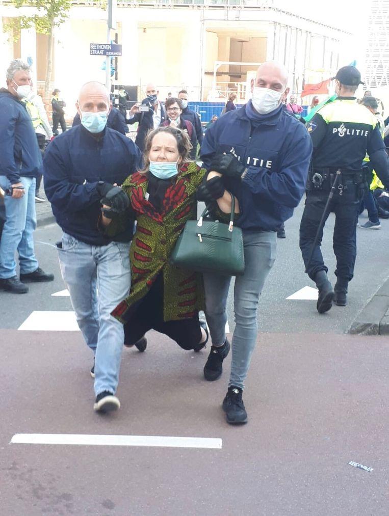 Een demonstrant wordt afgevoerd door de politie. Beeld Bart van Zoelen